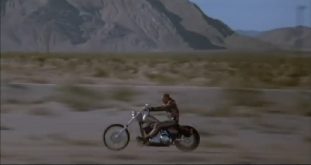 Harley Davidson motorcyle and rider travels through the desert highway.