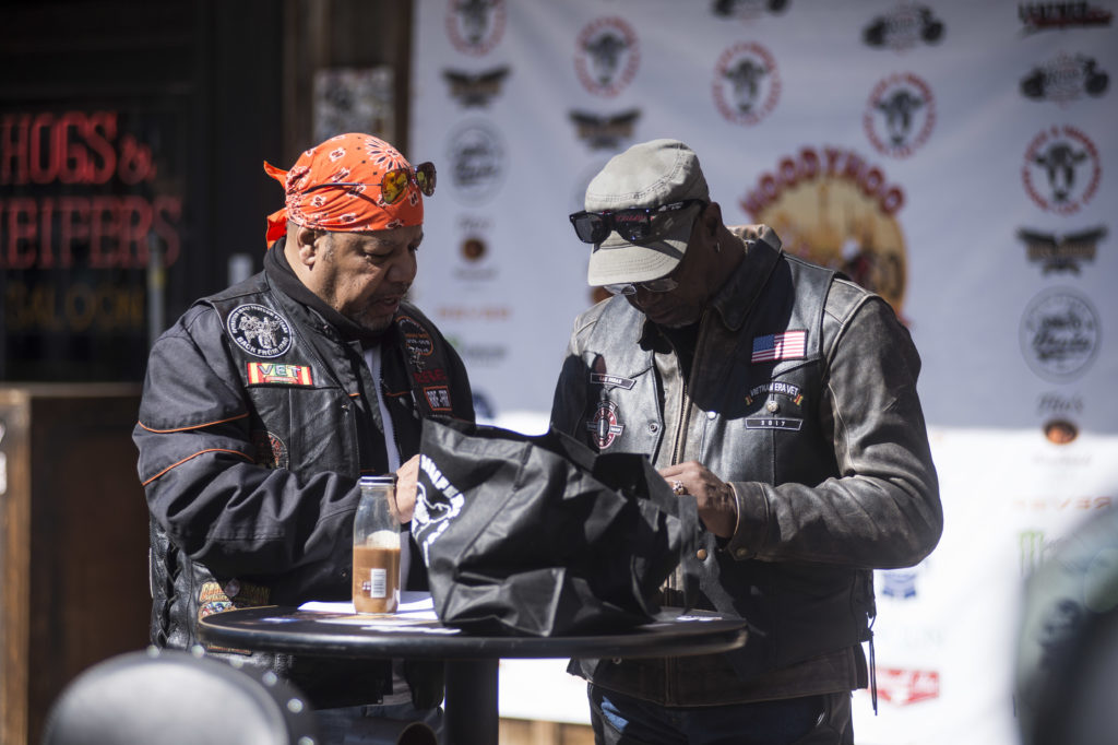 two motorcyclists looking at a cell phone, biker.