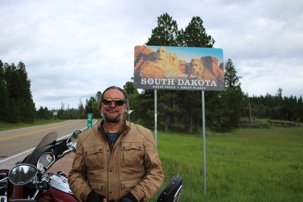 Dave Frey Veterans Charity Ride standing in front of south dakota sign heading to sturgis rally with motorcycle