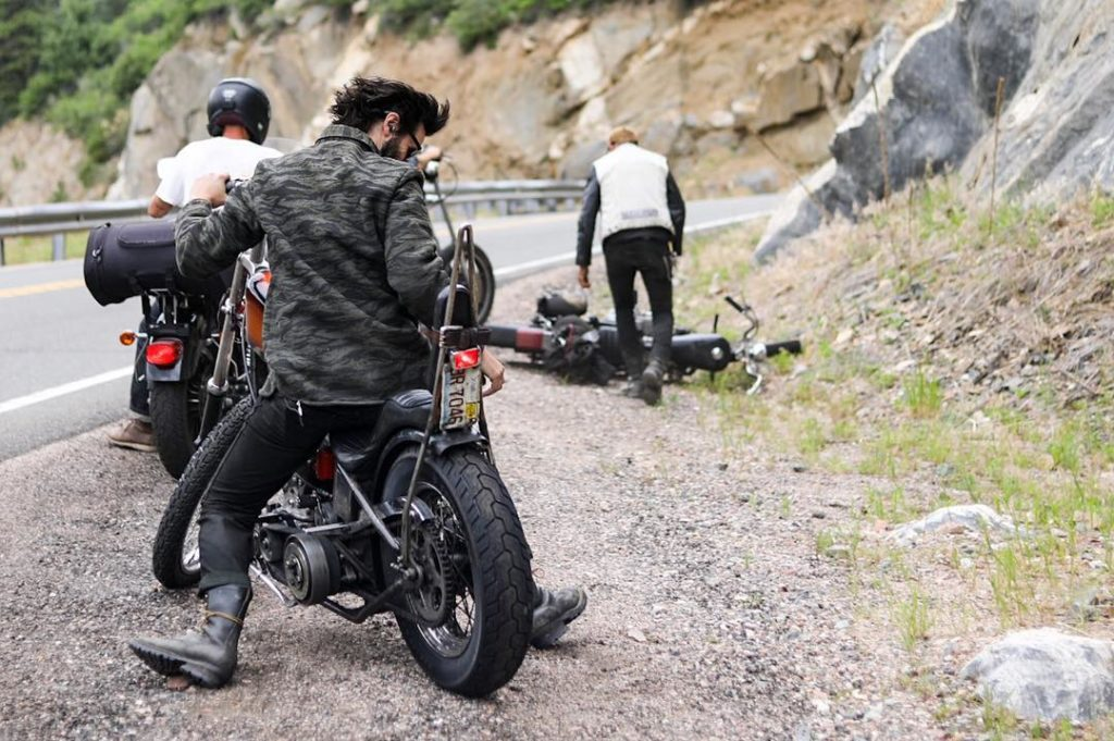 harley motorcycles and riders on side of mountain road